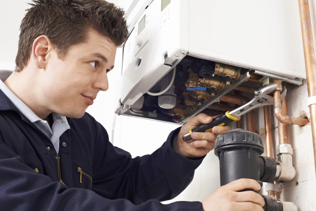 Male Working On Central Heating Boiler